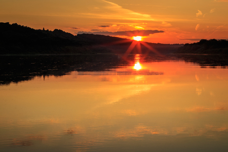 Scenic view of beautiful sunset above the river at autumn evening. Landscape.