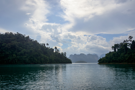 Lake Cheo Lan during the rain, Thailand. Landscape with a cloudy sky and karstic mountains in the background. Southeast Asia.