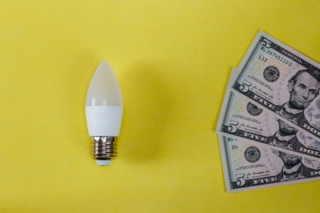 LED lamp on yellow background and dollar bills. The concept of saving money on electricity.