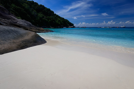A beautiful beach with white coral sand and turquoise sea on the Similan Islands on a sunny day. Landscape. Thailand.