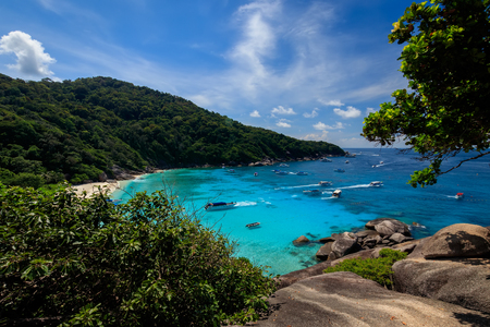 Observation site on the Similan Islands on a sunny day. Landscape. View of the beach and the sea from above. Trees and stones on a foreground. Stock Photo