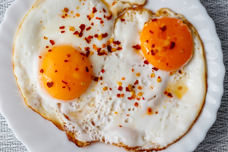 Fried eggs on a plate with chili peper spice on a table with a tablecloth. Reklamní fotografie