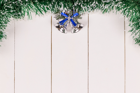 Christmas and New Year holiday background. Tinsel and christmas bell on white wooden table. Top view. Copy space. Flat lay.