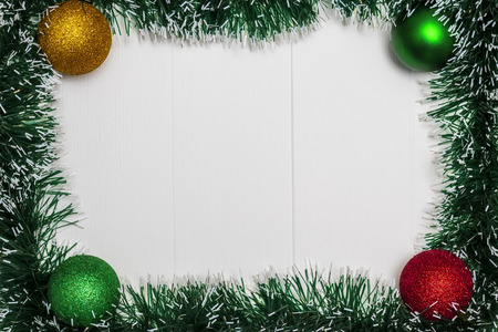 Christmas and New Year holiday background. Tinsel and christmas balls on white wooden table. Top view. Copy space. Flat lay. Archivio Fotografico