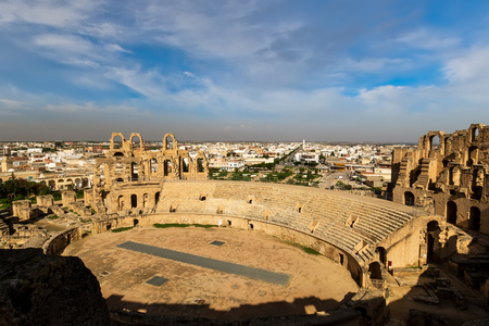 El Jem amphitheater in Tunisia on a sunny day with cloudy sky in a background.
