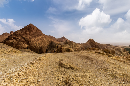 Landscape of a canyon in stone desert with cloudy sky on a background. Sahara gorge at sunny day. Tunisia.