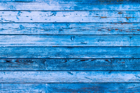 Blue texture of a board with peeling paint. Abstract background for design. Table or wall panel.