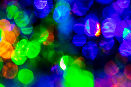Blured lights of garland, reflected in the crystal. Glowing texture. Abstract background for design.