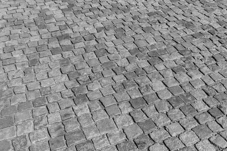 Top view on paving stone road. Old pavement of granite texture. Street cobblestone sidewalk. Abstract background for design.
