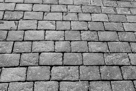 Vista dall'alto sulla strada lastricata. Vecchia pavimentazione di struttura del granito. Marciapiede di ciottoli di strada. Sfondo astratto per il design. Archivio Fotografico