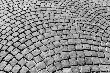 Draufsicht auf Pflastersteinstraße. Altes Pflaster der Granitbeschaffenheit. Gehweg mit Kopfsteinpflaster. Abstrakter Hintergrund für Design.