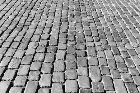 Vista superior de la carretera de adoquines. Pavimento antiguo de textura de granito. Acera de adoquines de la calle. Fondo abstracto para el diseño.