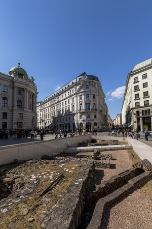 VIENNA, AUSTRIA- APRIL 22, 2019: Cityscape views of one of Europes town- Vienna. Roman city ruins on a foregrond and peoples on streets.