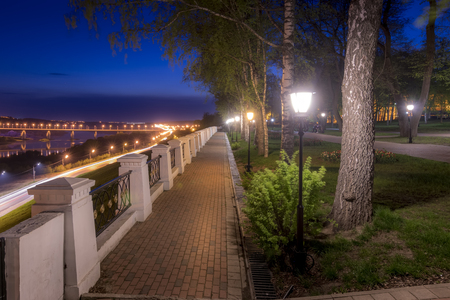 City night park in early summer or spring with pavement, young green leaves and trees. Bridge over the river and the road. Cityscape. Moving car with blur light. Фото со стока