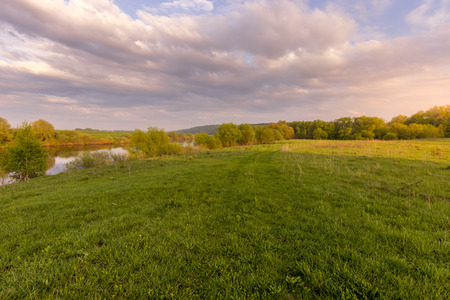 Sunset or dawn in a field with green grass, footpath, river and willows in the background. Early summer or spring. Landscape after rain with a light haze. Фото со стока