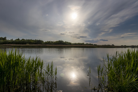 Scenic view of beautiful sunset or sunrise above the pond or lake at spring or early summer evening with cloudy sky background and reed grass at foreground. Landscape. Water reflection. Imagens