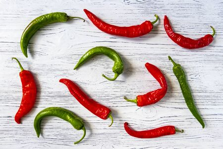 Hot red and green chili pepper on a white wooden vintage background.