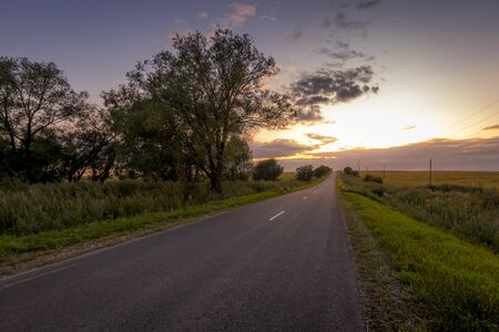 Asphalt road through agricultural fields at sunset on a summer or early autumn evening with a cloudy sky. Landscape.