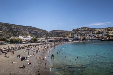 The sea coast and mountains of Matala on a clear summer sunny day with and a blue sky in the background. Crete, Greece. Sunbeds on the beach with tourists resting.