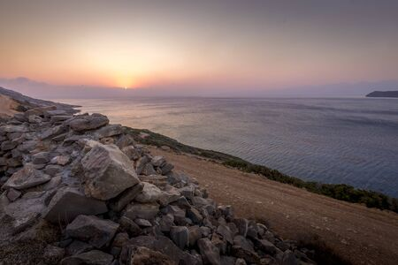 Twilight on the island of Crete near Spinalonga with a foggy horizon, sea, cliffs and dirt road on a summer morning.