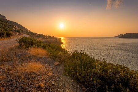 Sunrise on the island of Crete near Spinalonga with a foggy horizon, sea, cliffs and dirt road on a summer morning. 스톡 콘텐츠