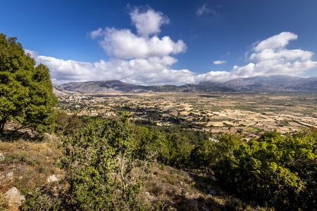 Top view of the Lassithi Plateau on a sunny clear day with trees in the foreground and a cloudy sky in the background. Crete island, Greece. Stock Photo