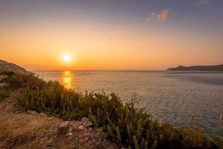 Dawn on the island of Crete near Spinalonga with a foggy horizon, sea, cliffs and dirt road on a summer morning.