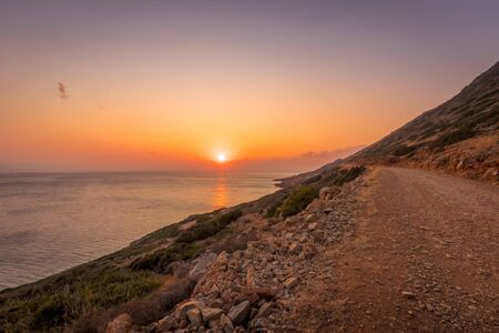 Dawn on the island of Crete with a foggy horizon, sea, cliffs and dirt road on a summer morning.