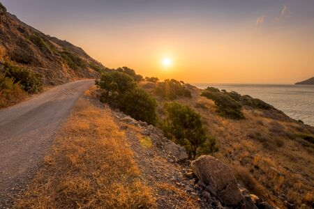 Dawn on the island of Crete near Spinalonga with sea coast and dirt road on a summer morning.