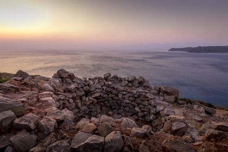 Twilight on the island of Crete near Spinalonga with a foggy horizon, sea coast, rocks and stones on a summer morning. Stock Photo