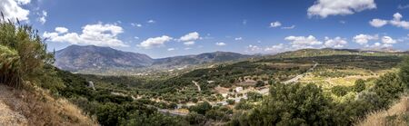 Panorama of mountains on the island of Crete on a clear sunny summer day with a cloudy sky. Greece.