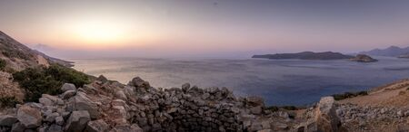 Twilight on the island of Crete with view to Spinalonga with a foggy horizon, sea coast, rocks and stones on a summer morning.