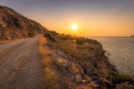 Sunrise on the island of Crete near Spinalonga with sea coast, rocks and dirt road on a summer morning. Stock Photo