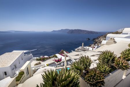 Oia city on Santorini island on a clear sunny day. Cliff overlooking the sea and the caldera.