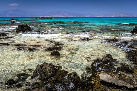 The coast of Chrissy island on a sunny summer day with turquoise sea water, a rocky bottom, black stones in the foreground and a blue clear sky with haze. Crete, Greece. Tropical seascape.