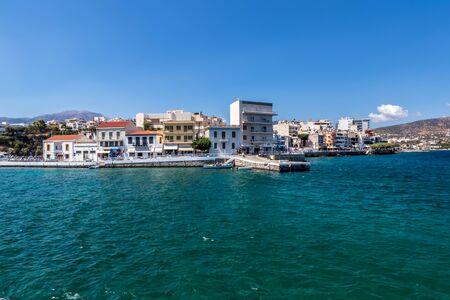Agios Nikolaus coastline on a sunny day with clear turquoise sea and cliffs. Crete, Greece, Aegean Sea.