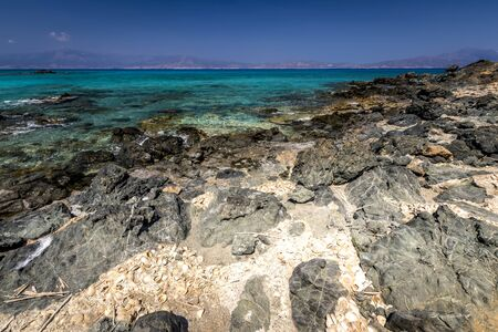 The coast of Chrissy island on a sunny summer day with turquoise sea water, a rocky bottom, yellow sand, black stones in the foreground and a blue clear sky with haze. Crete, Greece. Tropical seascape.