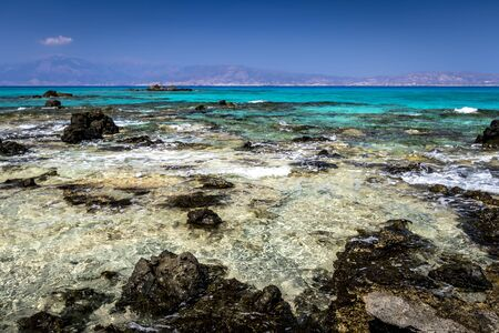 The coast of Chrissy island on a sunny summer day with turquoise sea water, a rocky bottom, black stones in the foreground and a blue clear sky with haze. Crete, Greece.