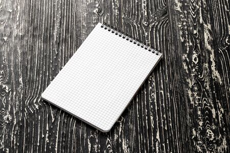 The notebook with squared pages on a black table with a copy space. Template for mock up and presentation design. Stock Photo - 138192027
