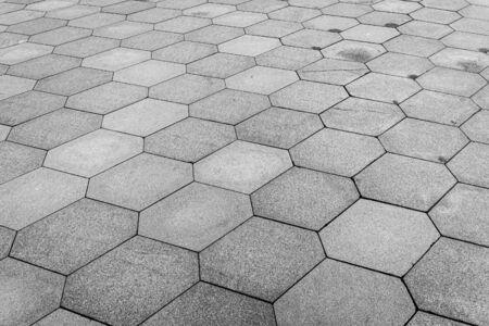 Vista superior de la carretera de adoquines. Pavimento antiguo de textura de granito. Acera de adoquines hexagonales de la calle. Fondo abstracto para el diseño. Foto de archivo