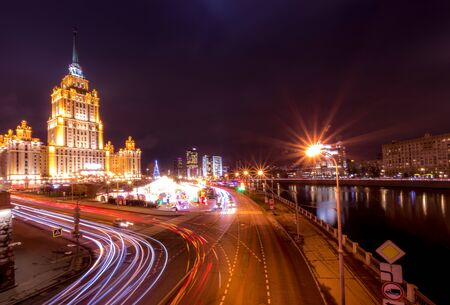 Moving car with blur light through city at night near Moscow river embankment and illuminated Radisson or Ukraine hotel. Moscow, Russia.