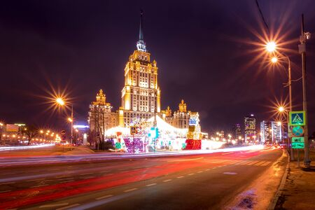 Moving car with blur light through city at night near Moscow river embankment and illuminated Radisson or Ukraine hotel. Moscow, Russia. Happy new year 2020 decoration in Russian. 에디토리얼