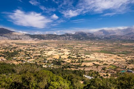 Top view of the Lassithi Plateau on a sunny clear day with a cloudy sky in the background. Crete island, Greece.