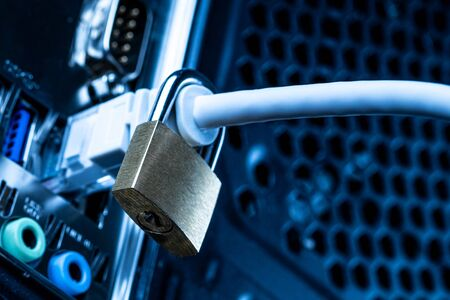 Closed lock hanging on a network cable plugged into a computer. The concept of security or blocking the Internet or the safety of personal data. Antivirus or firewall. Stock Photo