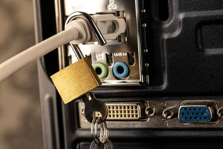 Opened lock hanging on a network cable plugged into a computer. The concept of opening access, unlocking the Internet or hacking anti-virus protection or firewall by hackers. Theft of personal data. Stock Photo