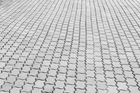 Top view on black and white paving stone road. Old pavement of granite texture. Street cobblestone sidewalk. Abstract background for design.