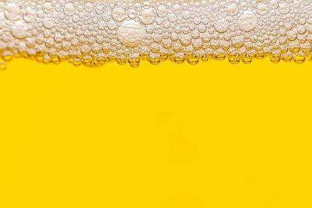 Texture of foam and gas bubbles in light beer. Abstract background for design.