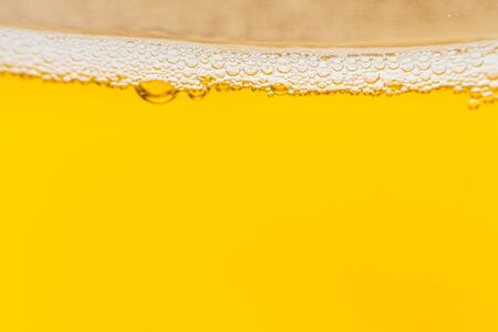 Texture of foam and bubbles in light beer. Abstract backdrop for design.