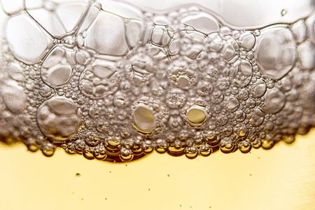 Texture of foam and bubbles in light beer. Abstract background for design.