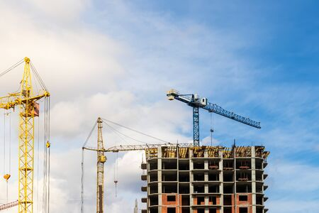 Boom cranes on a background of cloudy cloudy sky and building.
